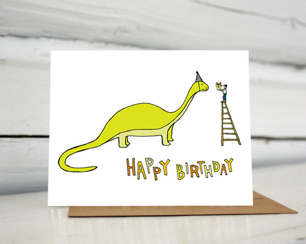 "A greeting card showing a hand-drawn illustration of a green brontosaurus wearing a party hat. A small boy stands on top of a ladder handing the dinosaur a wrapped birthday gift. A hand-lettered message reads, ""Happy Birthday."" Shown standing on a Kraft paper envelope in front of a white-washed log wall."