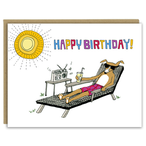 "A greeting card with a hand-drawn illustration of a dog in sunglasses and a floral bathing suit sitting in a lounge chair in the yard, drinking a tall glass of lemonade and listening to a boombox with one speaker while the sun shines overhead. A hand-lettered message reads, ""Happy Birthday!"" Shown with a Kraft paper envelope on a white background."