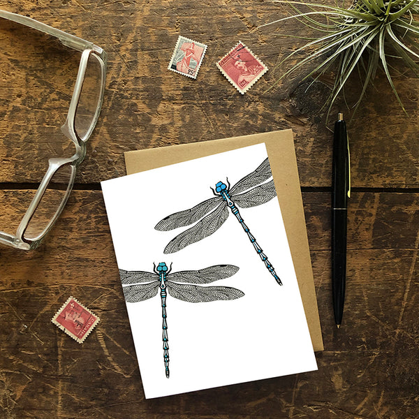A greeting card showing a hand-drawn ink illustration of two dragonflies, one with blue highlights and one with teal accents. Shown with a Kraft paper envelope on a worn wooden surface with reading glasses, stamps, a pen and an air plant.