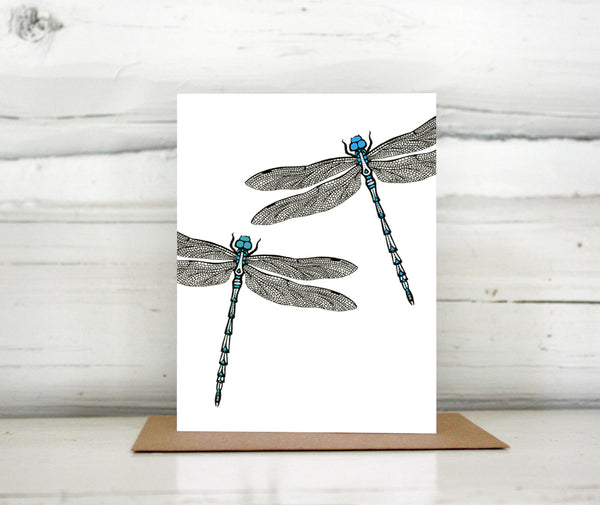 A greeting card showing a hand-drawn ink illustration of two dragonflies, one with blue highlights and one with teal accents. Shown standing on a Kraft paper envelope in front of a white-washed log wall.