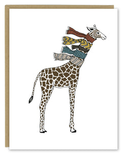 A greeting card showing a hand-drawn illustration of giraffe wearing five knit scarves on its neck. Shown with a Kraft paper envelope on a white background.