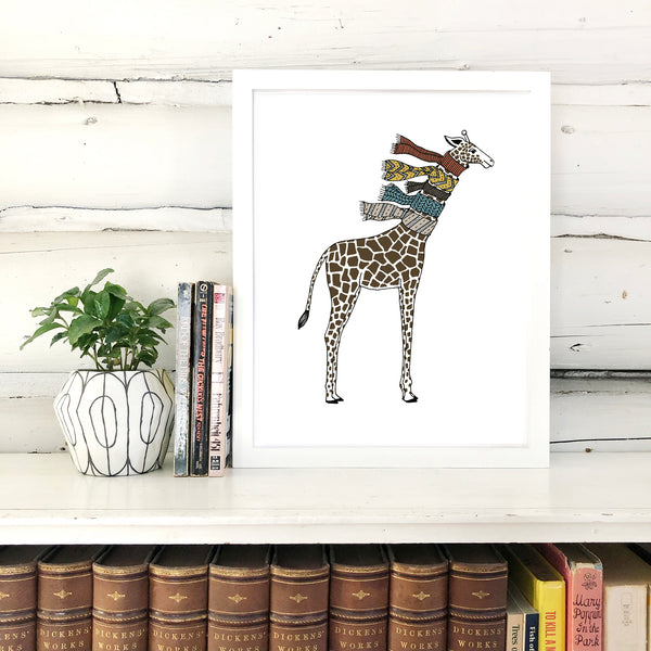A print of a hand-drawn illustration of giraffe wearing five knit scarves on its neck. Shown in a white frame on top of a bookcase with a potted plant and a few books, in front of a whitewashed log wall.