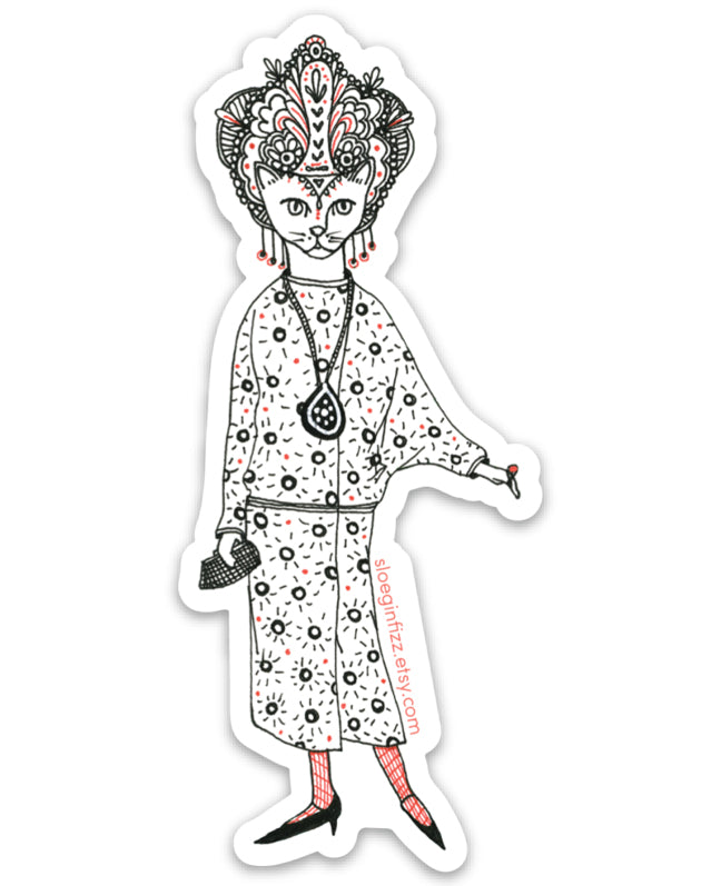 An illustrated die-cut vinyl sticker of a hand-drawn cat decked out in glamorous 1920s style, with a drop waist patterned dress, an elaborate headdress, dangly earrings and a clutch. She has a large pendant around her neck, red stockings and pointy shoes. Seen on a white background.