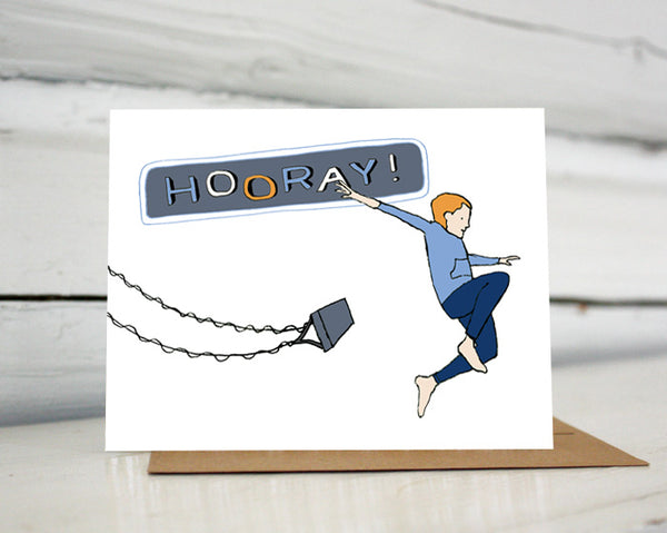 "A greeting card showing a hand-drawn illustration of a red-headed boy wearing navy blue pants and a blue gray sweatshirt, arms spread wide, jumping off a high-flying swing. ""Hooray!"" says the land-lettered message on the card. Shown standing on a Kraft paper envelope in front of a white-washed log wall."