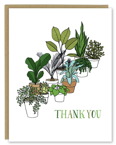 "A greeting card showing a hand-drawn illustration of a collection of houseplants. The card has a hand-lettered message reading, ""Thank You."" Shown with a Kraft paper envelope on a white background."