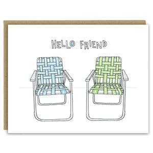 "A greeting card showing a hand-drawn illustration of a pair of old-fashioned lawn chairs with webbing and metal frames, one in blues and one in greens. A hand-lettered message reads, ""Hello Friend."" Shown with a Kraft paper envelope on a white background."