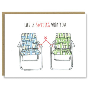 "A greeting card showing a hand-drawn illustration of a pair of old-fashioned lawn chairs with webbing and metal frames, one in blues and one in greens. A red thread ties the two chairs together and forms a small heart shape between them. A hand-lettered message reads, ""Life is sweeter with you."" Shown with a Kraft paper envelope on a white background."