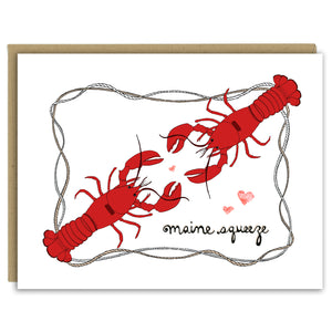"A greeting card with a hand-drawn ink illustration of two bright red lobsters facing each other with hearts around and a frame of nautical roping. The hand-lettered message reads, ""Maine Squeeze."" Shown with a Kraft paper envelope on a white background."