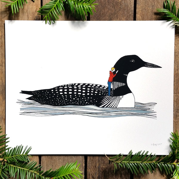 A print of a hand-drawn illustration of a black and white loon floating gently on the waves. A small woman with a yellow bob wearing jeans and a burnt orange hoodie stands on the loon's back with one hand resting on its neck. Shown on a wood background with evergreen branches around it.