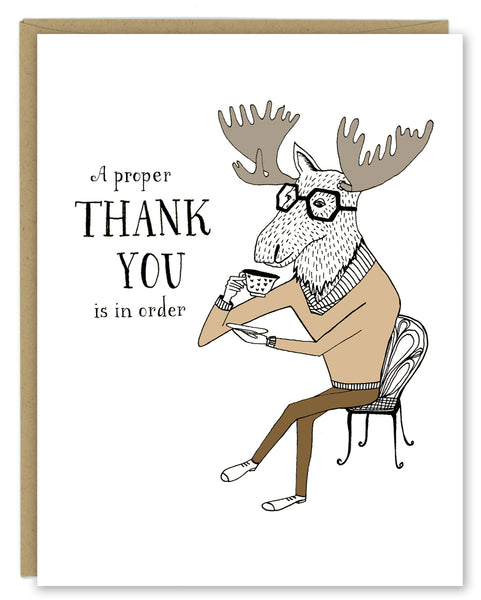 "A greeting card showing a hand-drawn illustration of a moose wearing a tan cowl-necked sweater, sitting cross-legged on a wire cafe chair, daintily raising a cup of tea to his mouth. A hand-lettered message reads, ""A proper thank you is in order."" Shown with a Kraft paper envelope on a white background."