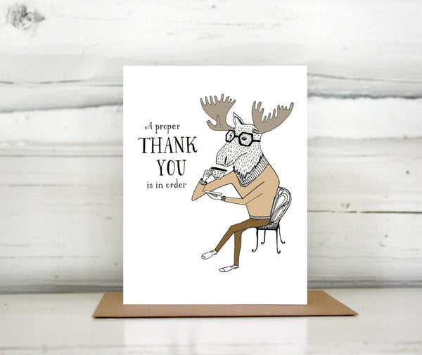 "A greeting card showing a hand-drawn illustration of a moose sitting cross-legged on a wire cafe chair, daintily raising a cup of tea to his mouth. A hand-lettered message reads, ""A proper thank you is in order."" Shown standing on a Kraft paper envelope in front of a white-washed log wall."