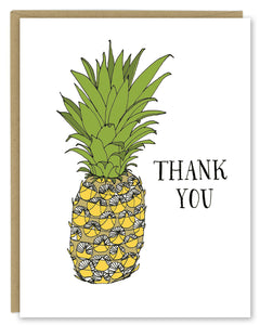"A greeting card showing a hand-drawn ink illustration of a pineapple with a hand-lettered message that reads, ""Thank You."" Shown with a Kraft paper envelope on a white background."