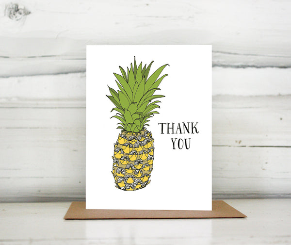 "A greeting card showing a hand-drawn ink illustration of a pineapple with a hand-lettered message that reads, ""Thank You."" Shown standing on a Kraft paper envelope in front of a white-washed log wall."