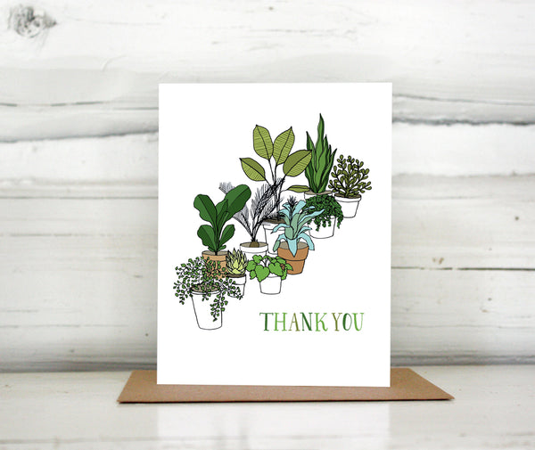 "A greeting card showing a hand-drawn illustration of a collection of houseplants. The card has a hand-lettered message reading, ""Thank You."" Shown standing on a Kraft paper envelope in front of a white-washed log wall."