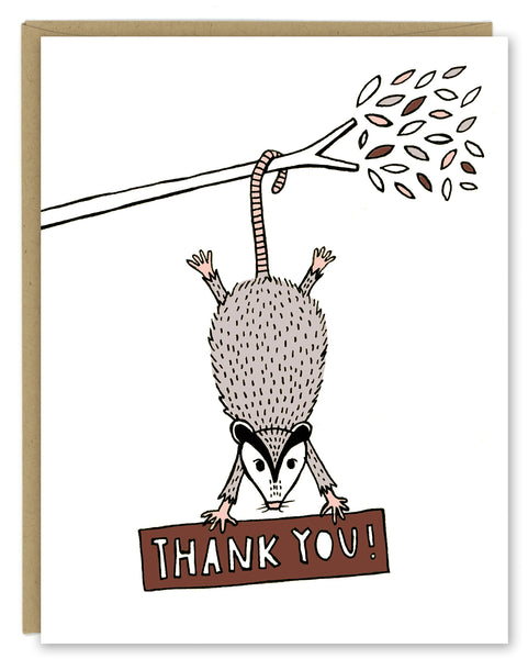 "A greeting card showing a hand-drawn illustration of a possum hanging from a tree branch hiding a sign with a hand-lettered message that reads,""Thank you!"" Shown with a Kraft paper envelope on a white background."