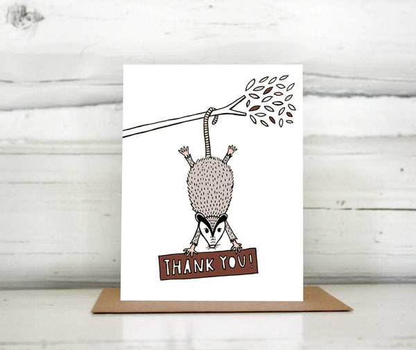 "A greeting card showing a hand-drawn illustration of a possum hanging from a tree branch hiding a sign with a hand-lettered message that reads,""Thank you!"" Shown standing on a Kraft paper envelope in front of a white-washed log wall."
