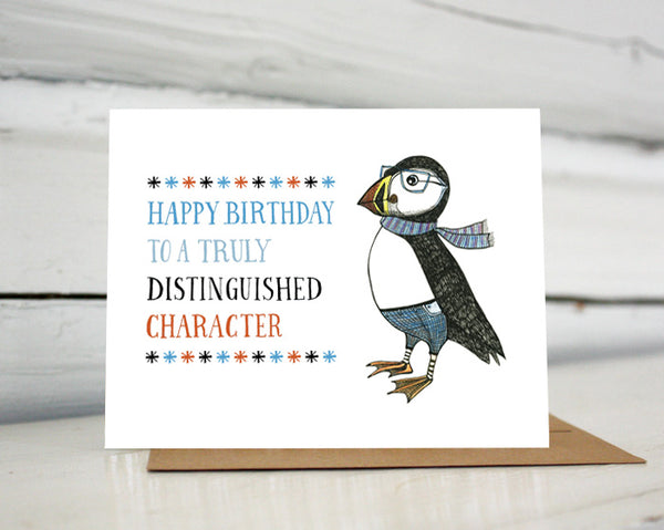 "A greeting card with a hand-drawn ink illustration of a dapper puffin wearing glasses, jeans and a scarf. A hand-lettered message reads, ""Happy Birthday to a truly distinguished character."" Shown standing on a Kraft paper envelope in front of a white-washed log wall."