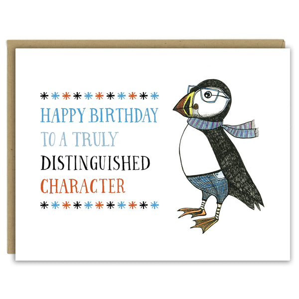 "A greeting card with a hand-drawn ink illustration of a dapper puffin wearing glasses, jeans and a scarf. A hand-lettered message reads, ""Happy Birthday to a truly distinguished character."" Shown with a Kraft paper envelope on a white background."