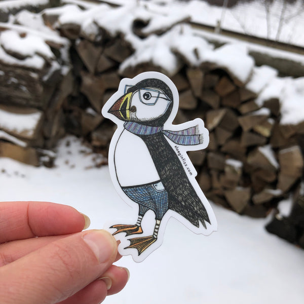 A hand holding up a sticker with a hand-drawn ink illustration of a dapper puffin in glasses, jeans and a scarf in front of a snowy background.
