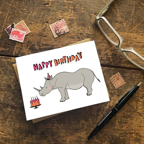 "A greeting card showing a hand-drawn illustration of a rhinoceros wearing a pink and black striped party hat that matches stripes on his horns, looking at an orange and pink birthday cake. A hand-lettered message reads, ""Happy Birthday."" Shown with a Kraft paper envelope on a worn wooden surface with reading glasses, stamps and a pen."