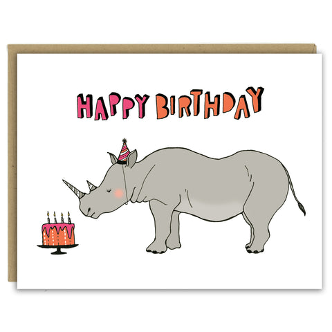 "A greeting card showing a hand-drawn illustration of a rhinoceros wearing a pink and black striped party hat that matches stripes on his horns, looking at an orange and pink birthday cake. A hand-lettered message reads, ""Happy Birthday."" Shown with a Kraft paper envelope on a white background."