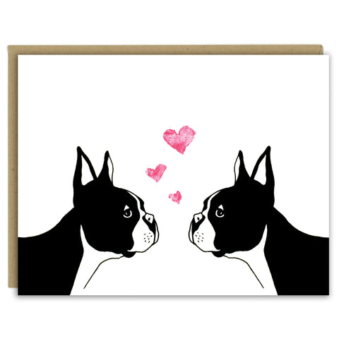 A greeting card with a hand-drawn illustration of two Boston terriers facing each other with three little hearts rising above their heads. Shown with a Kraft paper envelope on a white background.