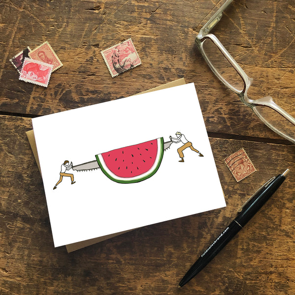 A greeting card shows a pair of loggers sawing off a slice of a giant watermelon in a hand-drawn illustration. Seen with a Kraft paper envelope on a wood surface with stamps, a pen and reading glasses.