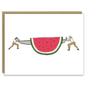 A pair of loggers saws off a slice of a giant watermelon in a hand-drawn illustration on a greeting card. Seen with a Kraft paper envelope on a white background.
