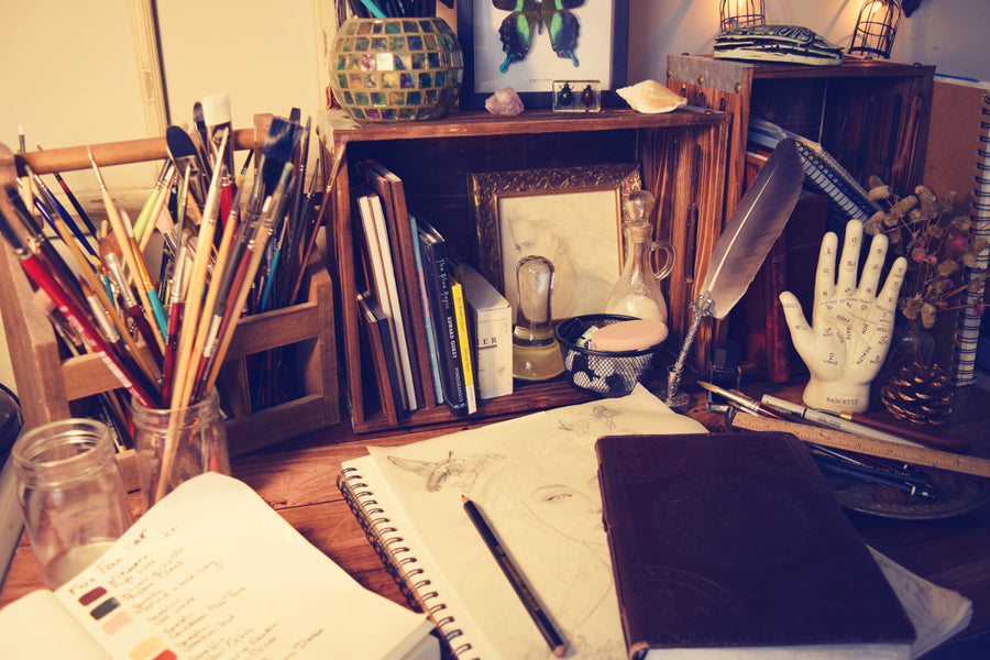 my painting desk in my art studio with supplies and sketchbook