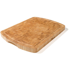 Load image into Gallery viewer, A beautiful handcrafted extra large bamboo chopping board made from end grain bamboo. Each piece is unique with bamboo strips set against one another creating a quite gorgeous pattern. Rounded finger grips on the ends allow you to easily pick it up. A juice groove runs around the edge to collect liquids preventing them from spilling on to your kitchen counter and keeping surfaces clean for you.