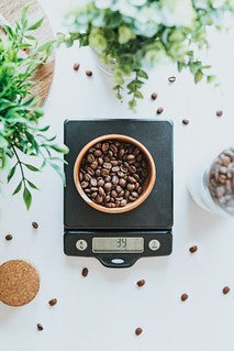Weighing coffee beans on scales