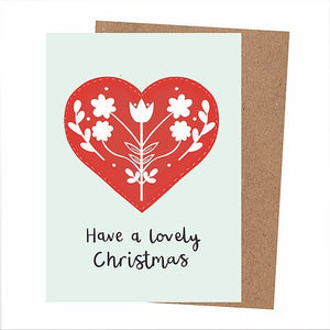 Off-white greetings card with danish folk inspired heart design, with a white floral pattern. Below are the handwritten words 'Have a lovely Christmas' in black.