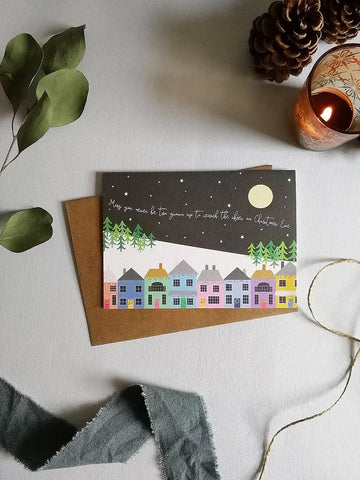 Christmas card and envelope, with a seasonal, colourful village scene, with the words 'may you never be too grown up to search the skieso n Christmas Eve' flying through the moonlit night sky. Card is set against a white textile backgrouns with winter themed items.