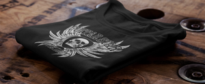 Guitar Star Clothing Skull and Wings T-shirt on wooden surface, folded presentation
