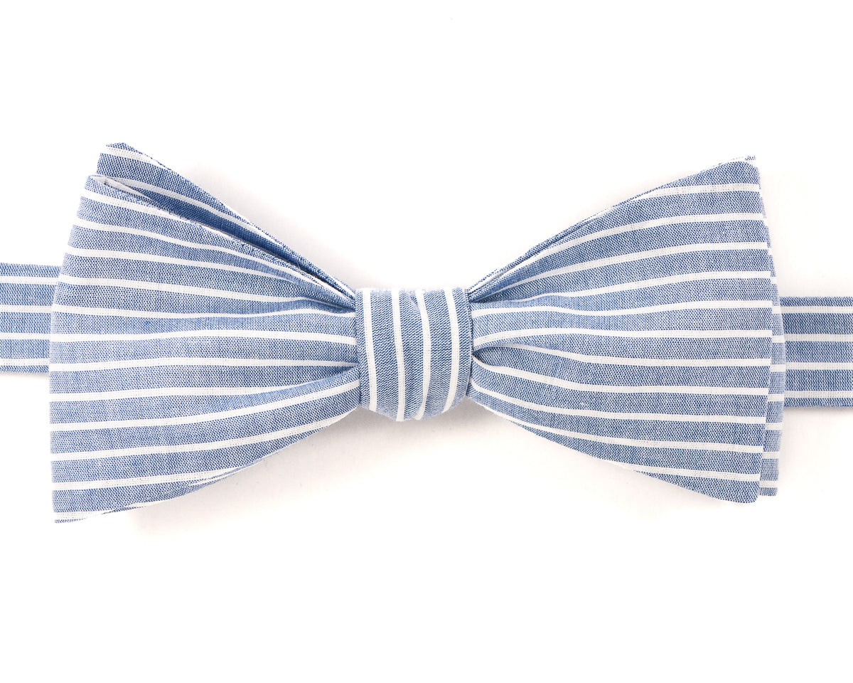 "100% Cotton Light Blue w/ White Stripes Self Tie Bow Tie Classic Butterfly Shape Adjustable from 14.5""-18"" Handmade in Seattle, WA Didn't find the right color or size? Special event, party, school formal or wedding that needs a bespoke bow tie?   We'd love to custom make your perfect bow tie. Shoot us an email and we'll work with you to find the right fit."