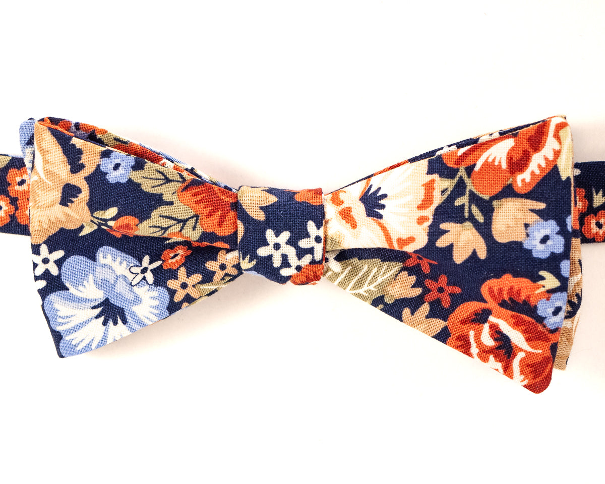 "100% Cotton Navy Blue w/Floral Print Self Tie Bow Tie Classic Butterfly Shape Adjustable from 14.5""-18"" Handmade in Seattle, WA    Didn't find the right color or size? Special event, party, school formal or wedding that needs a bespoke bow tie?   We'd love to custom make your perfect bow tie. Shoot us an email and we'll work with you to find the right fit."