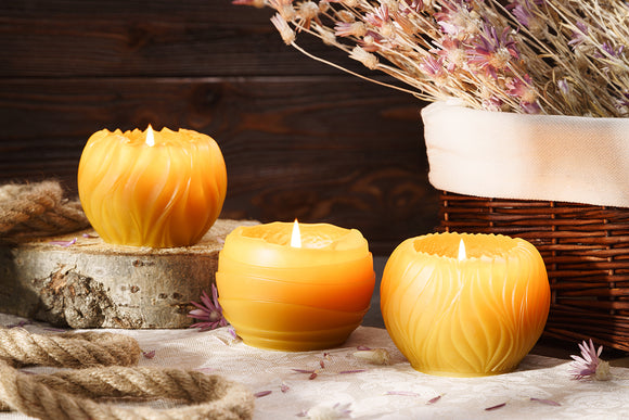 three pure beeswax round candles burning
