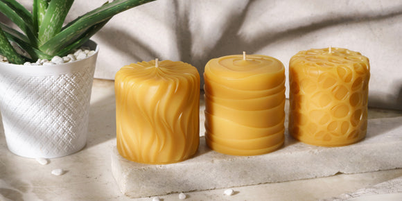 three decorative beeswax candle pillars
