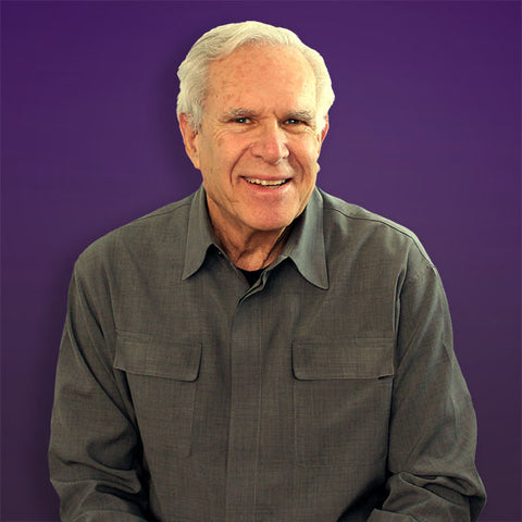 Smiling man poses against purple background