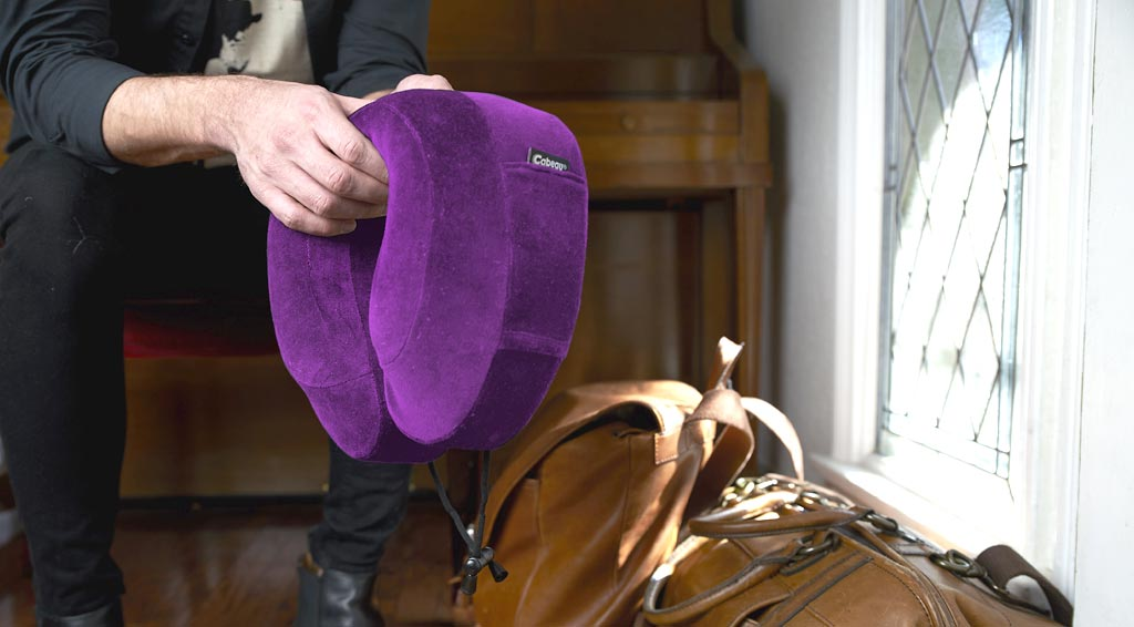 Man holds purple travel neck pillow