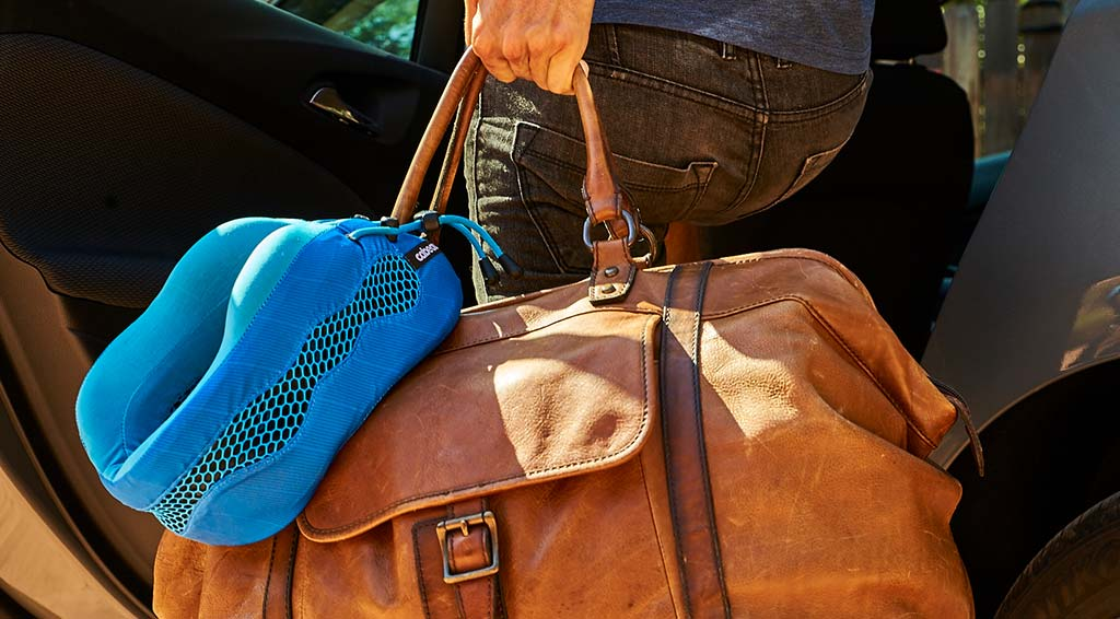 Cabeau Evolution Cool neck pillow attached to a leather duffel bag