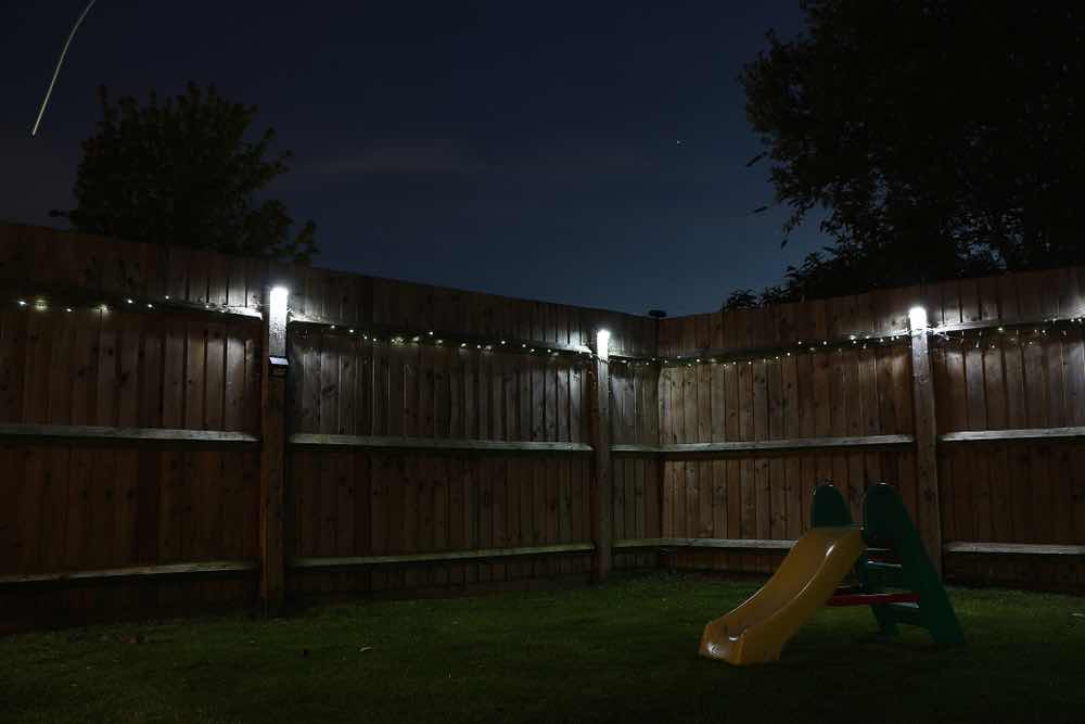 solar lights hung on a backyard fence