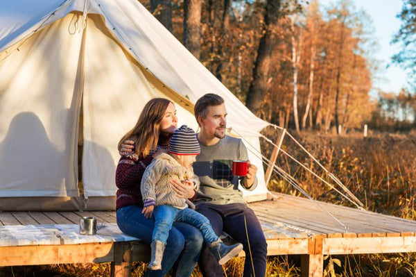 family sitting in front of glamping tent