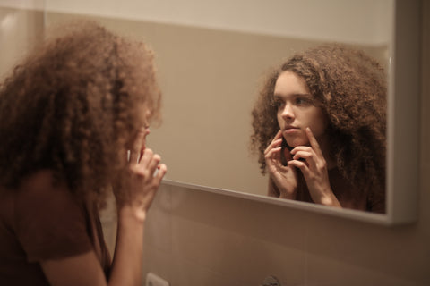 Woman looking stressed while looking at her skin in the mirror