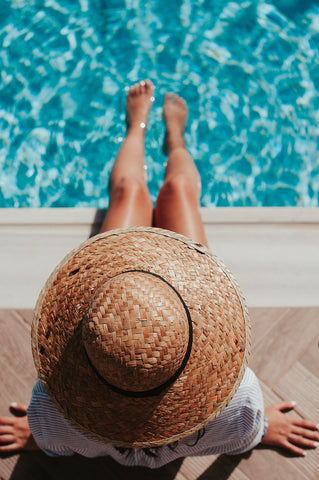 Girl wearing a straw hat with toes in a pool
