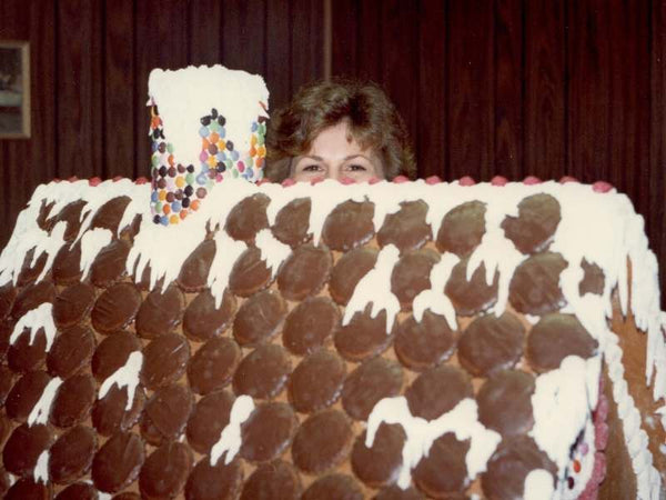 Janet (Nona) hiding behind a huge ginger bread house.