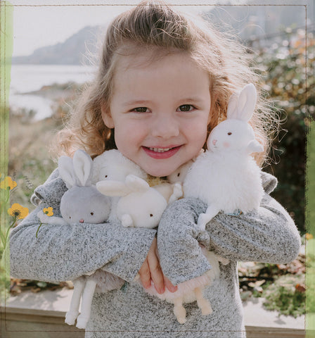 Little Girl Holding Stuffed Bunnies