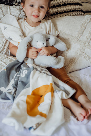 Little Girl Snuggling With Stuffed Bunny and Blanket