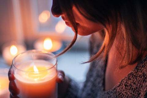 woman from the chest up, holding a lit candle.