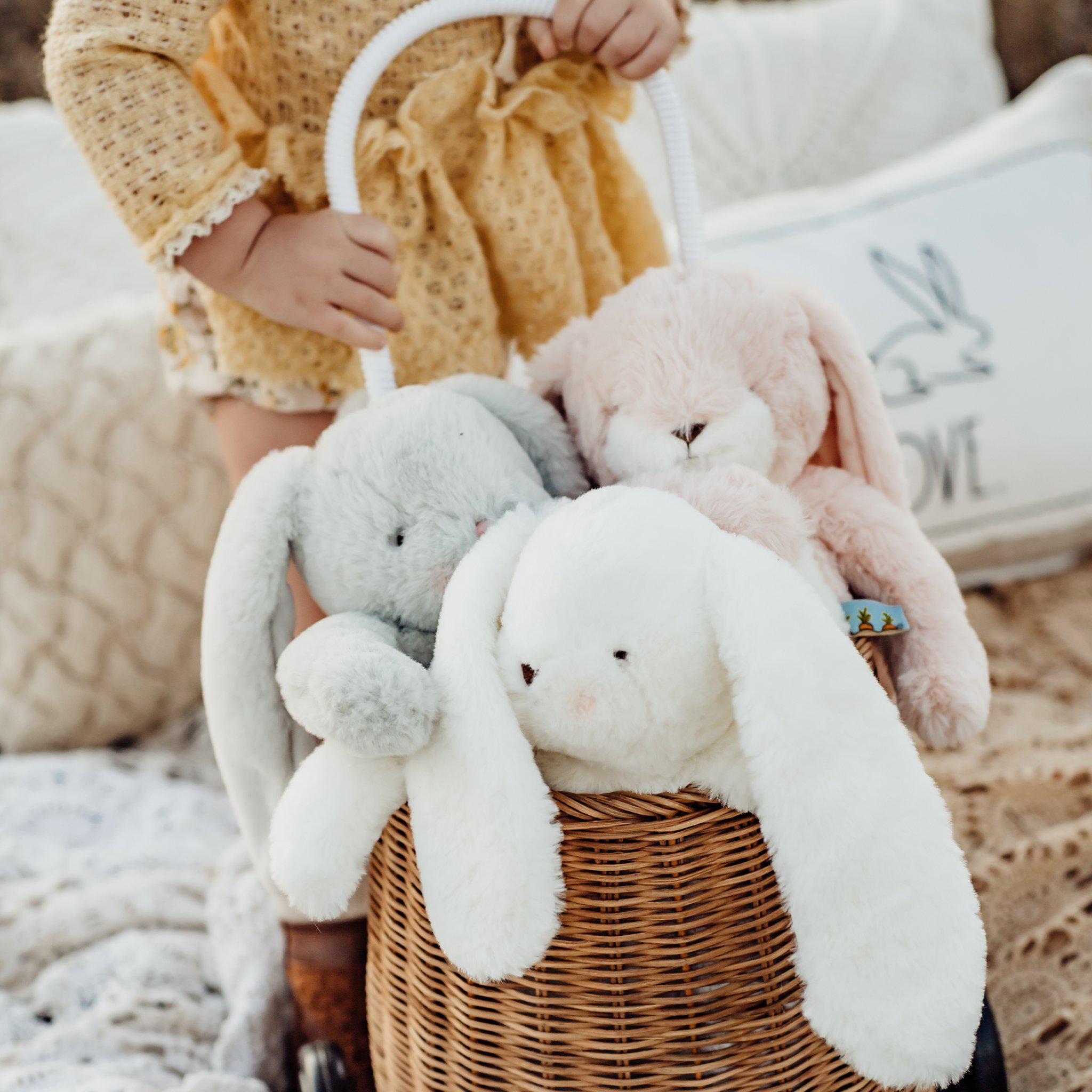 A bunch of plush bunnies pulled on a cart by a toddler